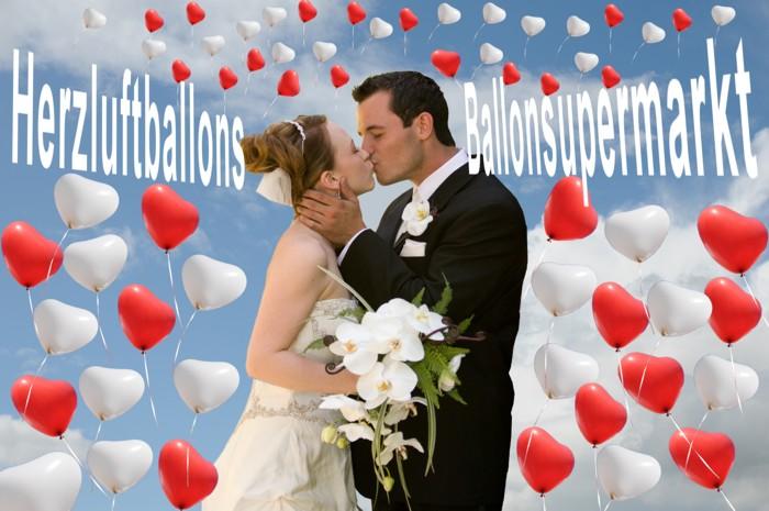 Glückliches Hochzeitspaar mit aufsteigenden Herzluftballons